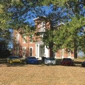 Several Corvettes parked on the lawn in front of Whtie Hall